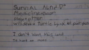"Photo, page of a child's notebook reading ""I don't want this land to hurt no more"""
