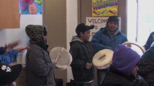 Photo of children beating hand drums.