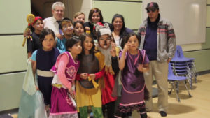 Photo of Jackie Hookimaw-Witt with children of Attawapiskat taking part in performance art inspired by indigenous ways of learning.